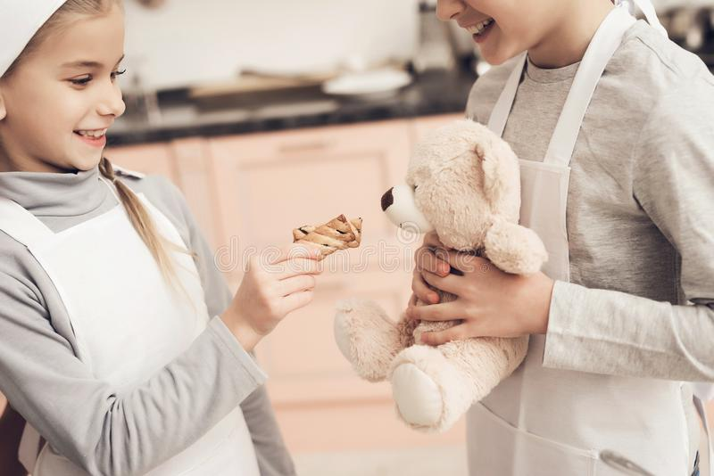 Children with mother in kitchen. Kids are giving cookie to teddy bear. Children in chef`s hats with mother in kitchen. Kids are giving cookie to teddy bear royalty free stock photography