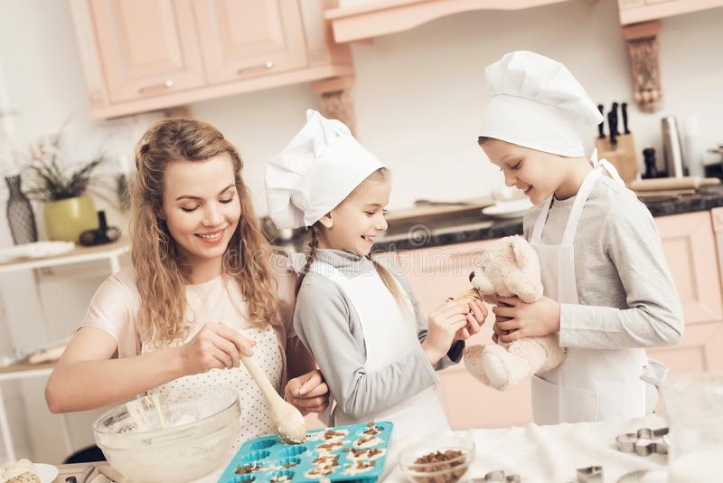 Children with mother in kitchen. Kids are giving cookie to teddy bear. Children in chef`s hats with mother in kitchen. Kids are giving cookie to teddy bear stock photos