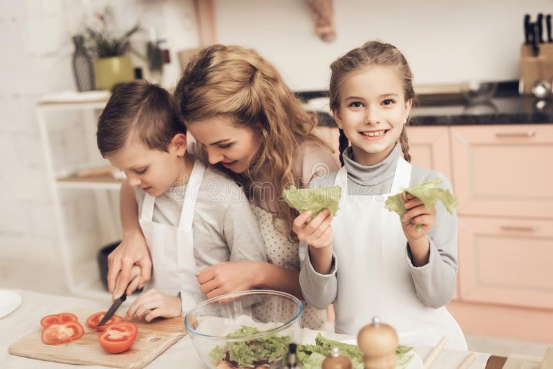 Children with mother in kitchen. Mother is helping kids prepare vegetables for salad. Children with mother at kitchen table in kitchen. Mother is helping kids royalty free stock photos