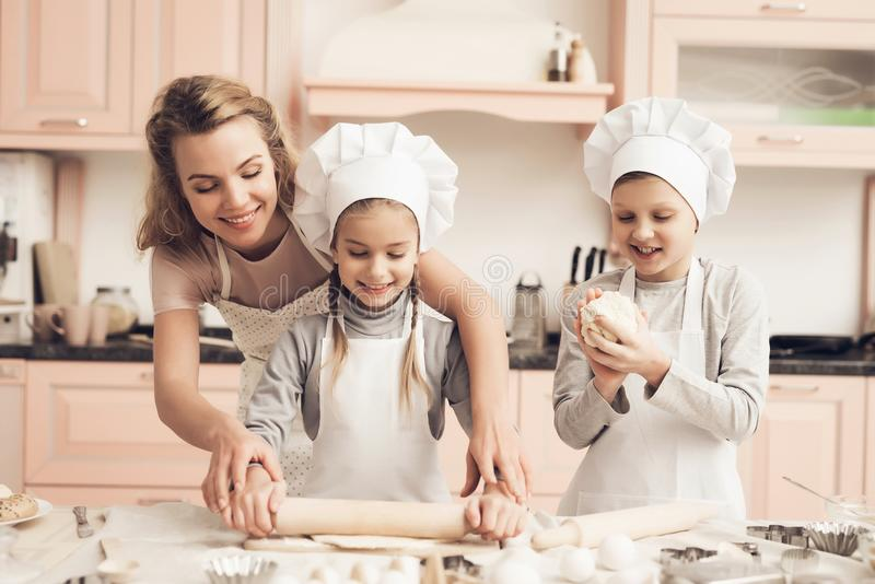 Children with mother in kitchen. Mother is helping kids to roll out dough. Children in chef`s hats with mother in kitchen. Mother is helping kids to roll out stock photography