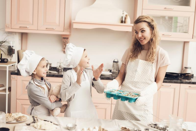 Children with mother in kitchen. Mother is holding baking dish with dough. Children in chef`s hats with mother in kitchen. Mother is holding baking dish with royalty free stock images