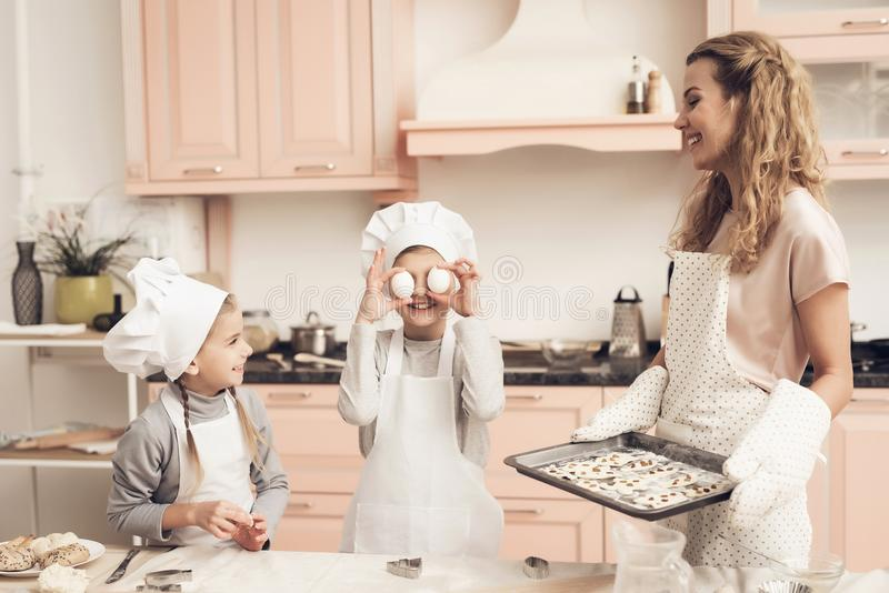 Children with mother in kitchen. Mother is holding tray with cookies. Children in chef`s hats with mother in kitchen. Mother is holding tray with cookies royalty free stock photography