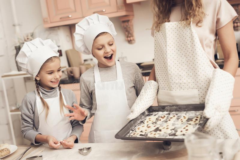 Children with mother in kitchen. Mother is holding tray with cookies. Children in chef`s hats with mother in kitchen. Mother is holding tray with cookies royalty free stock photo