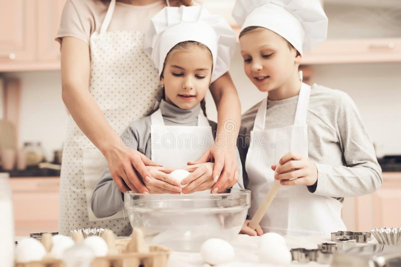 Children with mother in kitchen. Mother is teaching kids how to break eggs. stock photos