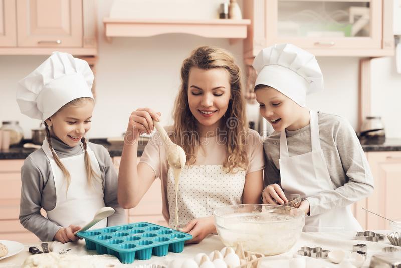 Children with mother in kitchen. Mother is teaching kids how to put dough in baking dish. Children in chef`s hats with mother in kitchen. Mother is teaching royalty free stock photos