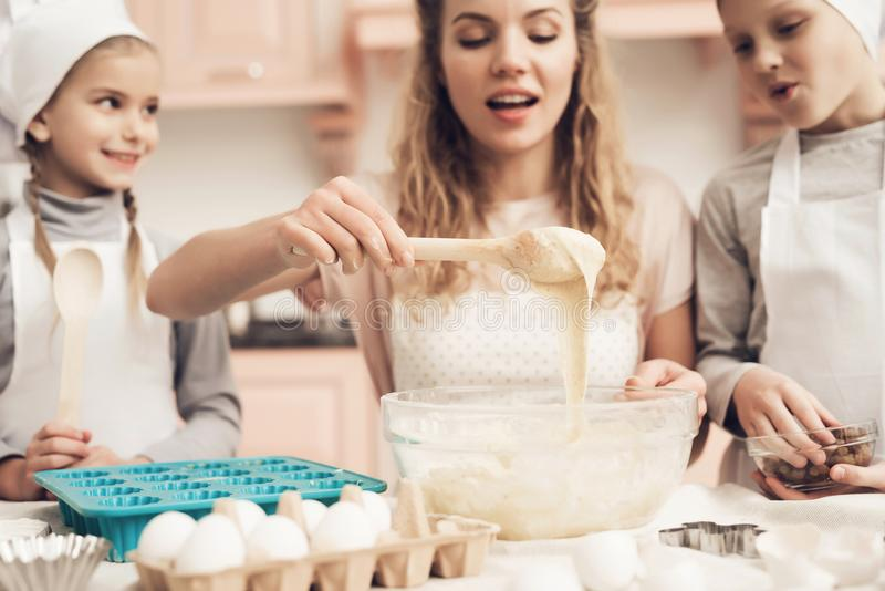 Children with mother in kitchen. Mother is teaching kids how to put dough in baking dish. Children in chef`s hats with mother in kitchen. Mother is teaching stock photography