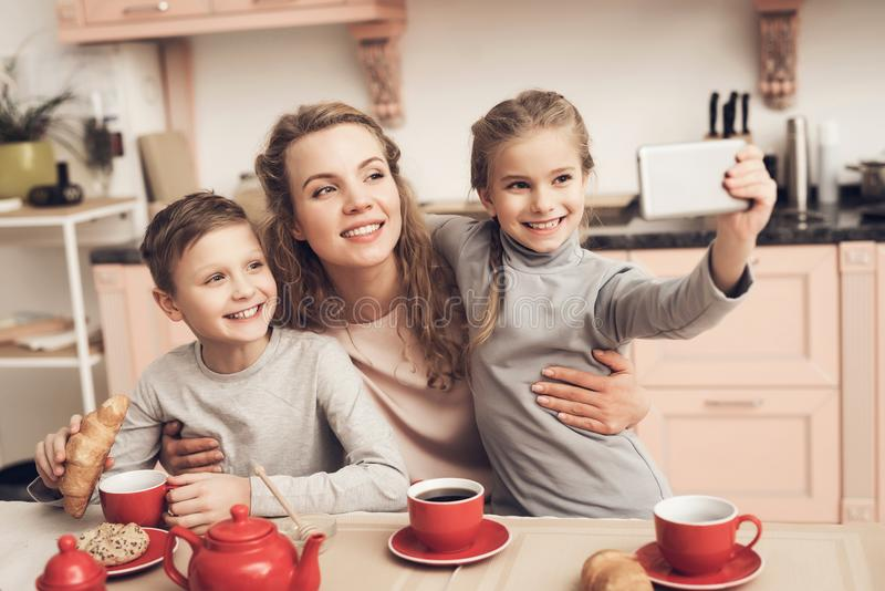 Children with mother in kitchen. Family is driking tea and taking selfie on phone. Children with mother at kitchen table in kitchen. Family is driking tea and royalty free stock photos