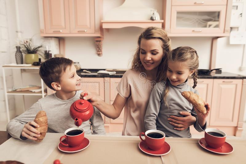 Children with mother in kitchen. Family is drinking tea with croissants. Children with mother at kitchen table in kitchen. Family is drinking tea with royalty free stock photography