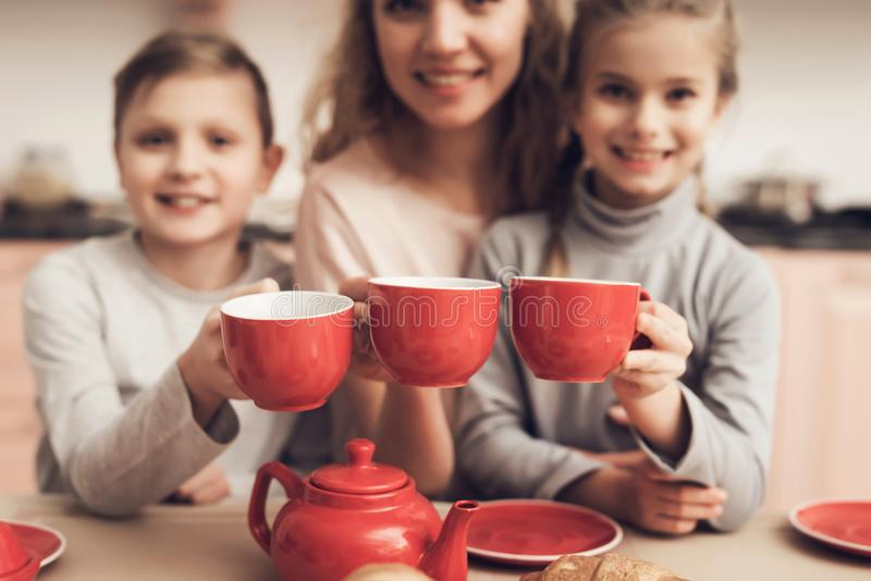 Children with mother in kitchen. Family is holding cups with tea. Children with mother at kitchen table in kitchen. Family is holding cups with tea royalty free stock image
