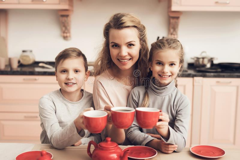 Children with mother in kitchen. Family is holding cups with tea. Children with mother at kitchen table in kitchen. Family is holding cups with tea royalty free stock images