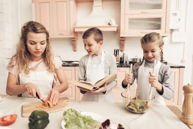 Children with mother in kitchen. Kids are helping mother to make salad. royalty free stock photos