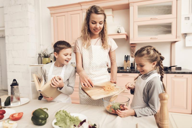 Children with mother in kitchen. Kids are helping mother to make salad. Children with mother at kitchen table in kitchen. Kids are helping mother to make salad stock photography