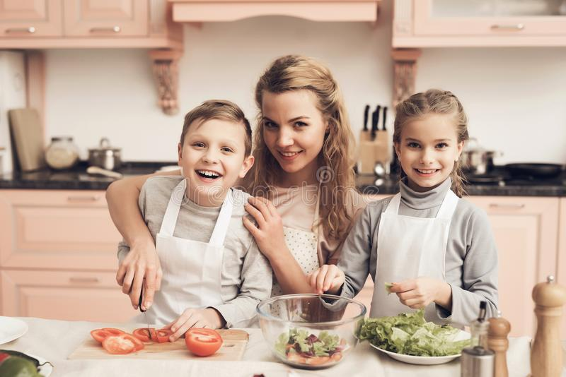 Children with mother in kitchen. Mother is helping kids prepare vegetables for salad. stock image