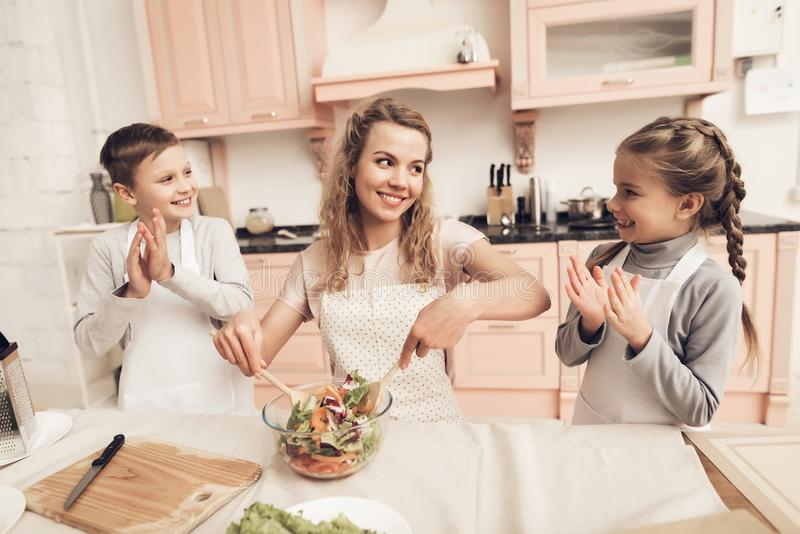 Children with mother in kitchen. Mother is making salad and kids are watching. Children with mother at kitchen table in kitchen. Mother is making salad and kids royalty free stock photos