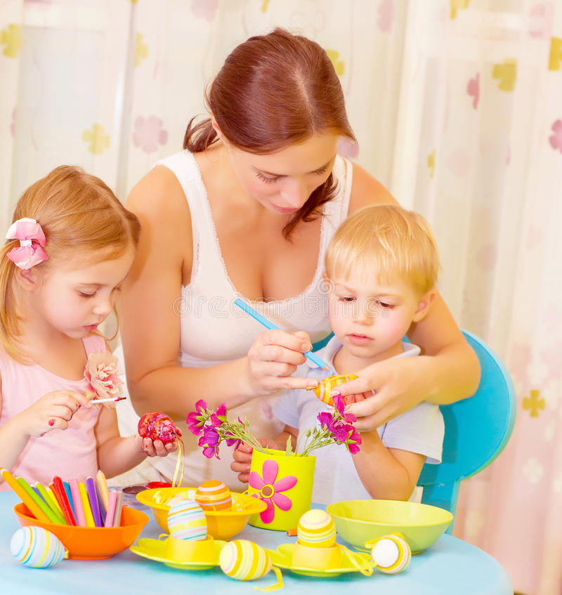 Children with mother paint eggs stock photography