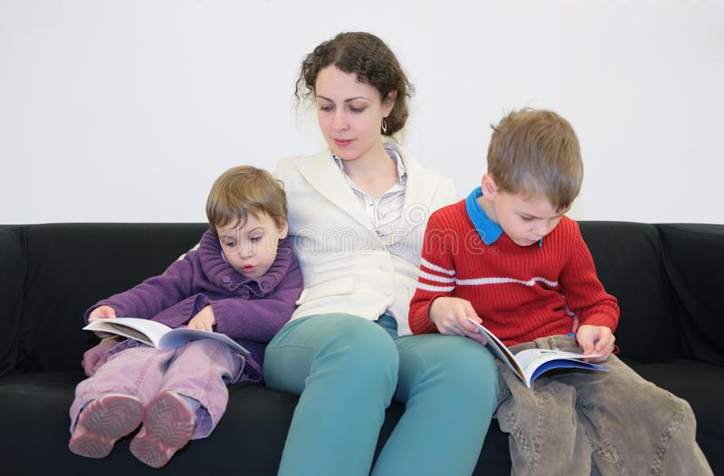 Children With Mother Read Books On Sofa Free Stock Photo