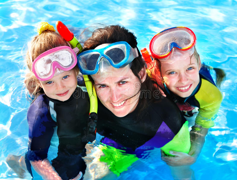 Children with mother in swimming pool. stock images