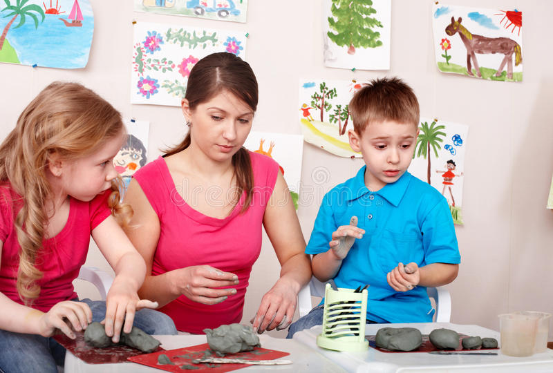 Children mould with teacher from clay. royalty free stock images