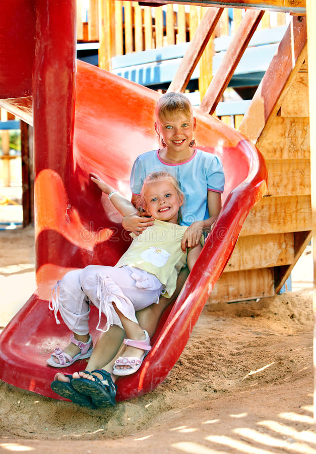 Children Move Out To Slide In Playground. Stock Photos