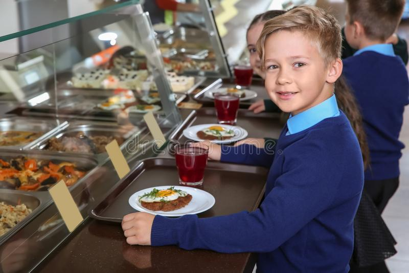 Children near serving line with healthy food in canteen royalty free stock photos