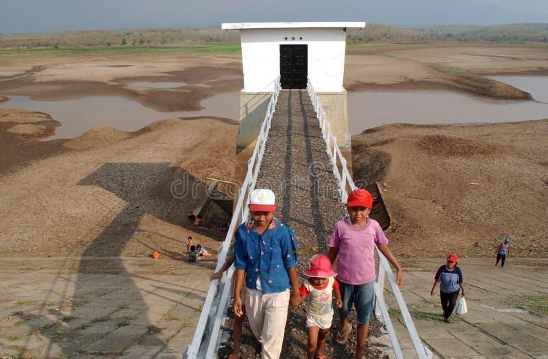 Children near the storage reservoir Dawuhan, Wonoasri, Madiun. Children play in the Dawuhan water storage reservoir, Wonoasri, Madiun, East Java, Indonesia on royalty free stock image
