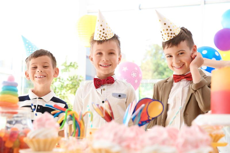 Children near table with treats at birthday party indoors. Cute children near table with treats at birthday party indoors royalty free stock images