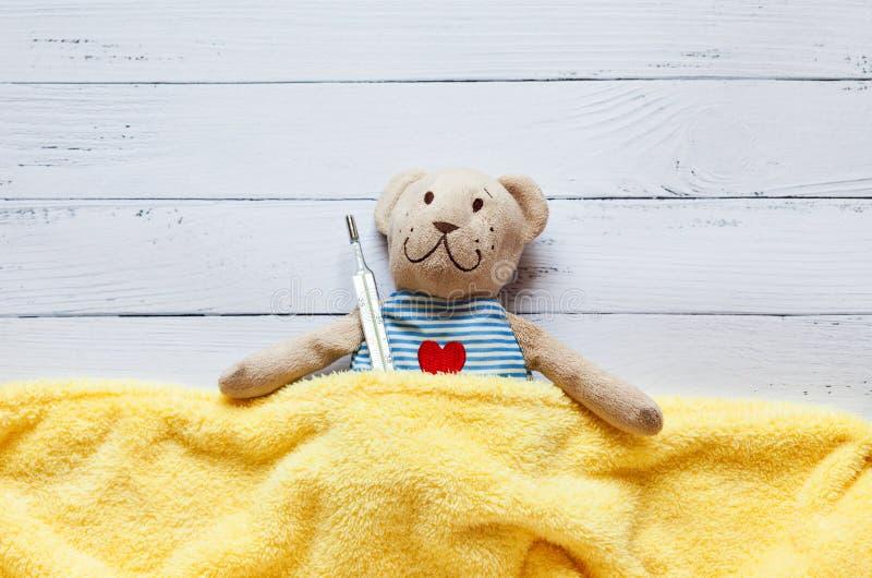 Children& x27; nehmen weicher Spielzeugteddybär s im Bett mit Thermometer und Pillen, die Temperatur eines Quecksilberglases Auf  stockbild