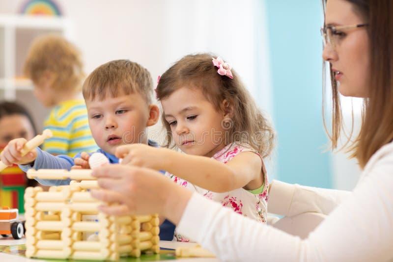 Children and nursery teacher building toy house in kindergarten royalty free stock image