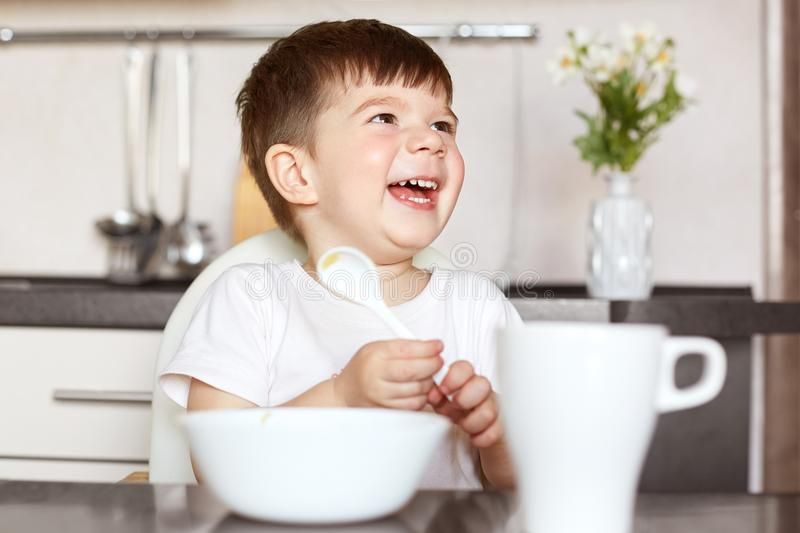 Children and nutrition concept. Smiling delighted small cute kid eats tasty cereals and drinks tea, being in good mood, looks happ stock photos