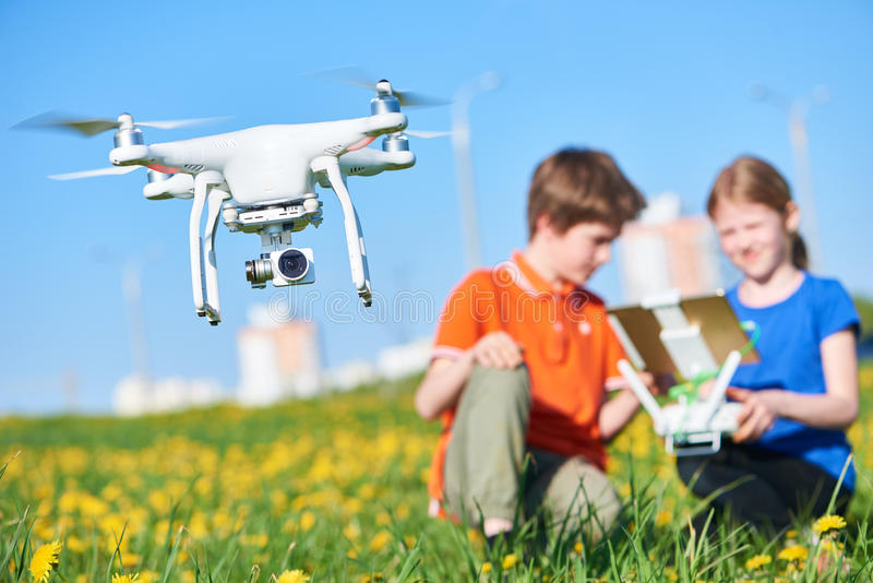 Children operating of flying drone at sunset stock photography