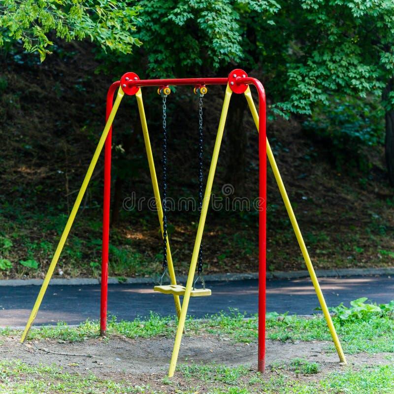 Children& x27; os balanços de s penduram vazio uma quietude em um campo de jogos em um dia maçante, nublado fotografia de stock