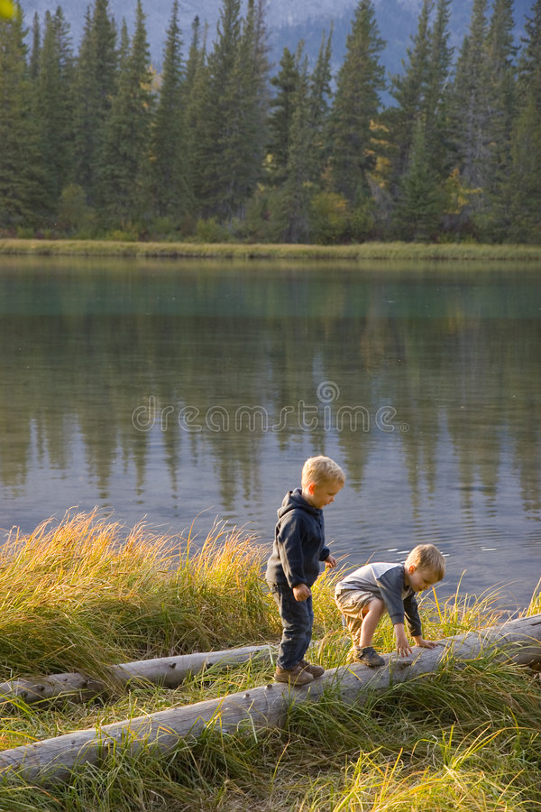 Children outdoors. Two children play outdoors on logs near a calm river (Bow River near Canmore, Alberta, Canada