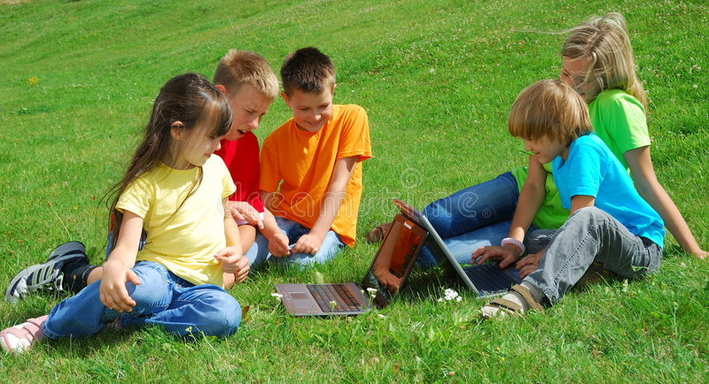 Children outdoors with laptops. Group of happy children relaxing in a grassy meadow studying the screens of two laptop computers royalty free stock photography