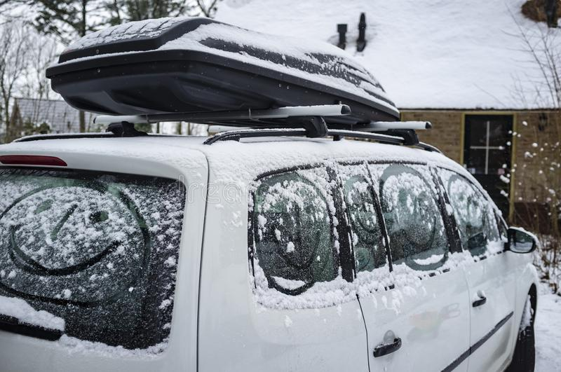 Children painted a smiling face on the snow-covered windows of the car, against the background of a country house. Family holidays stock images