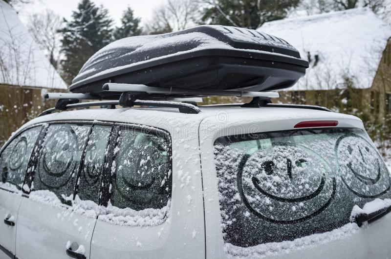 Children painted a smiling face on the snow-covered windows of the car, against the background of a country house. Family holidays stock photos