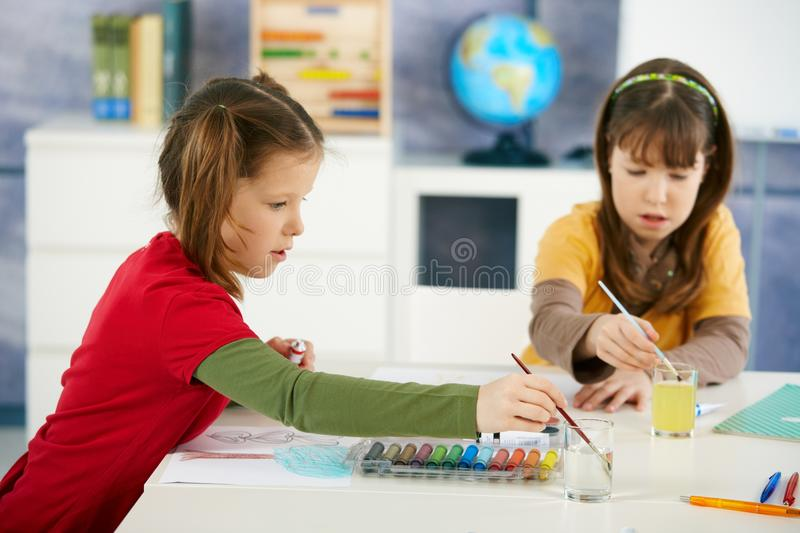 Children painting in art class. Elementary age children sitting around desk enjoying painting with colors in art class at primary school classroom royalty free stock photography