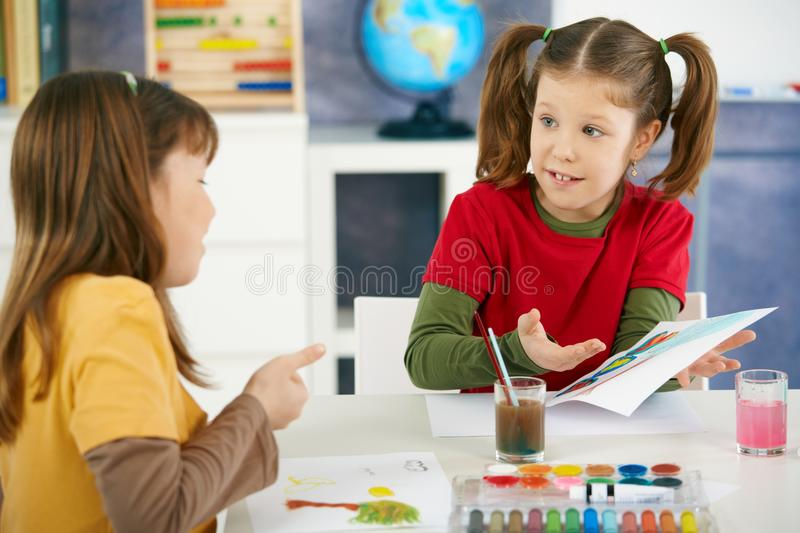 Children painting in art class. Elementary age children sitting around desk enjoying painting with colors in art class at primary school classroom stock image