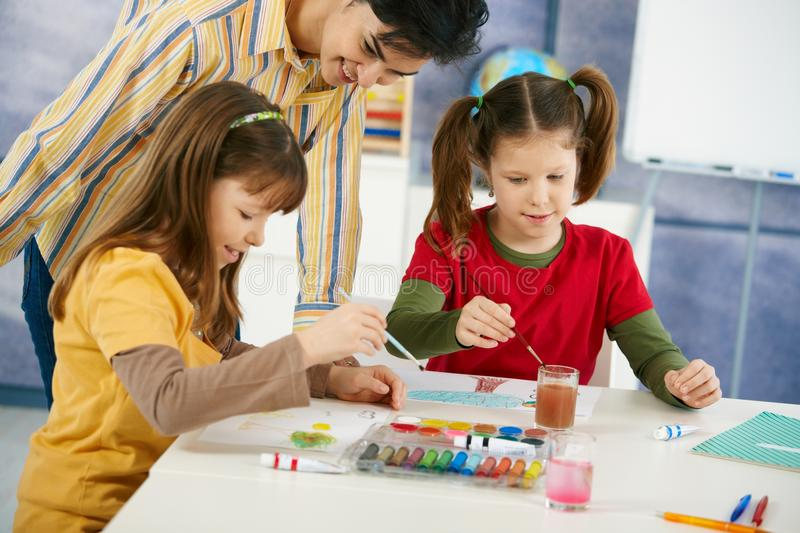 Children painting in art class. Elementary age pupils sitting around desk enjoying painting with colors in art class at primary school classroom stock images