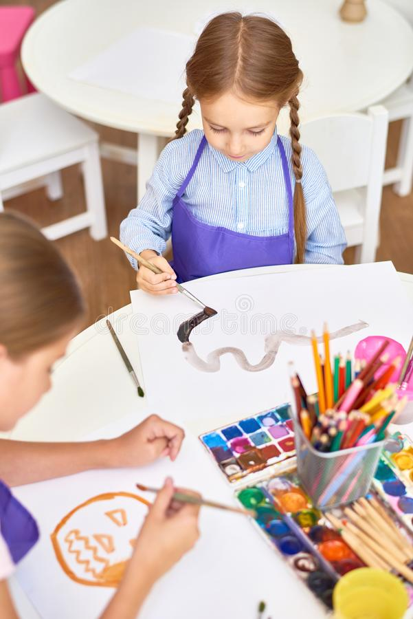 Children Painting in Art Class. High angle portrait of two girls painting pictures on Halloween enjoying art lesson in development school royalty free stock photos