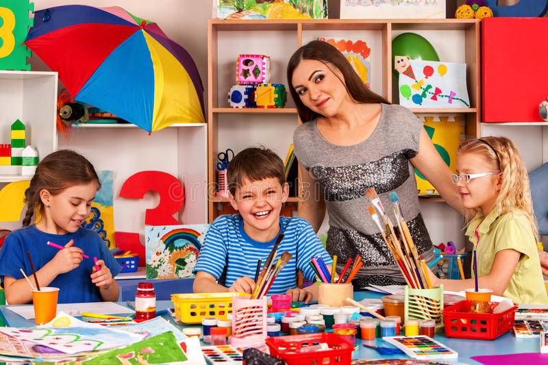 Children painting and drawing together . Craft lesson in primary school. Kids playroom organization of children painting and drawing in kid`s club. Craft lesson royalty free stock image