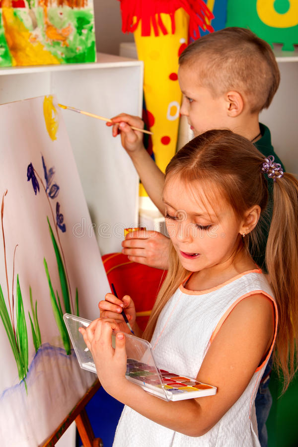Children painting finger on easel. Group of kids alone in class school. Children painting on easel. Girl with boy learn paint alone in class school. Child royalty free stock image