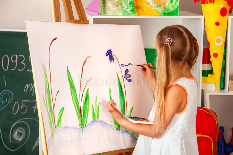 Children painting finger on easel. Group of kids with teacher. stock photography