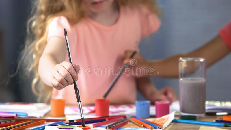 Children painting with gouache at art lesson in primary school, childhood stock image