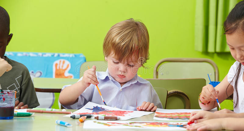 Children painting in kindergarten stock images