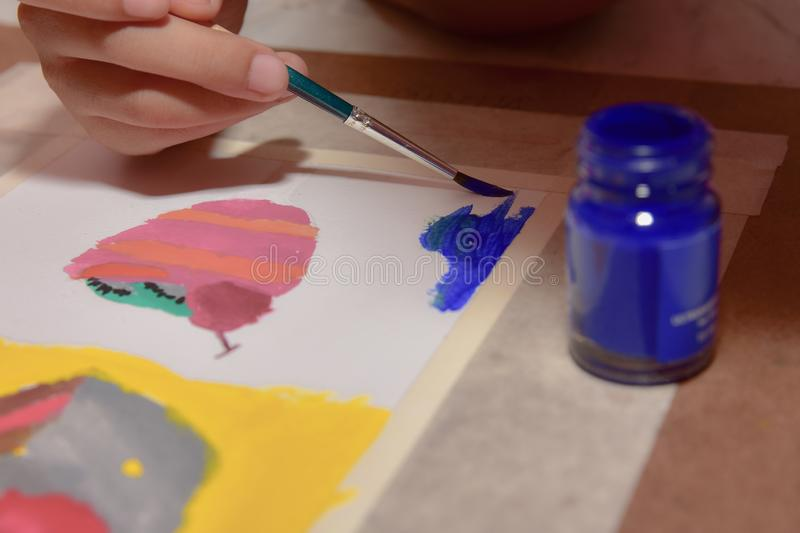 Children painting with paintbrush on white paper stock image