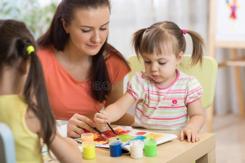 Children painting in preschool. Teacher helps by little girl. royalty free stock image