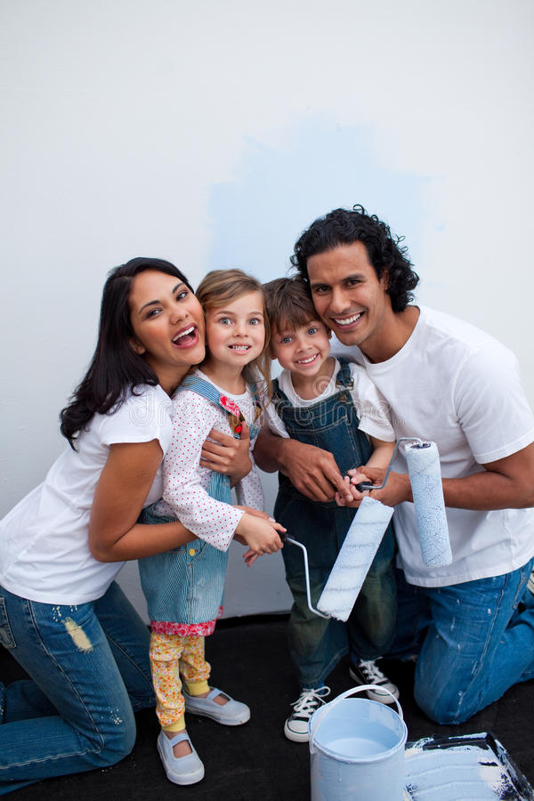 Children Painting A Room With Their Parents Stock Photo
