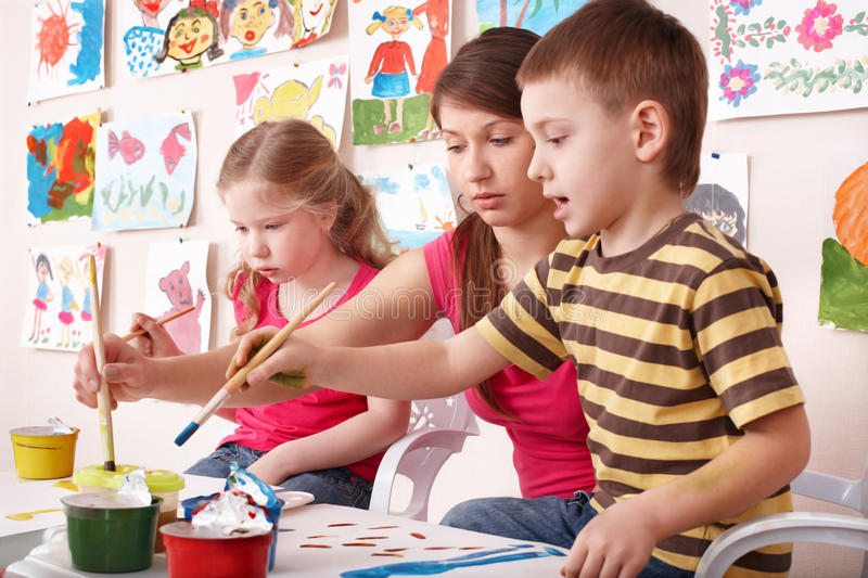 Children painting with teacher in art class. Child care royalty free stock image