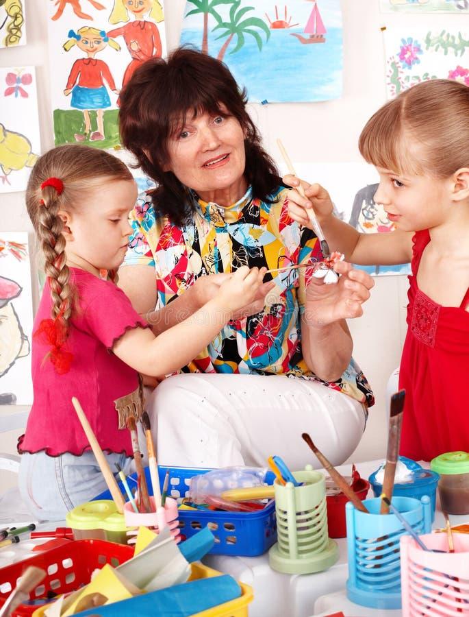 Children painting with teacher in preschool. stock photo