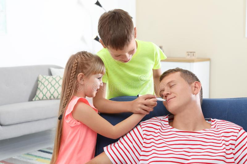 Children painting their father`s face while he sleeping royalty free stock photos